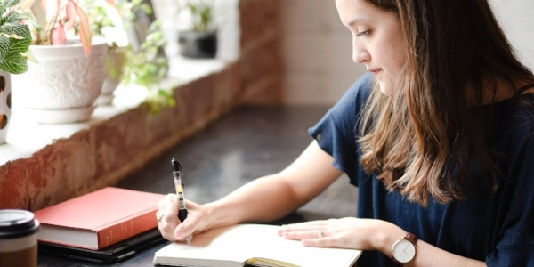 woman-writing-in-journal-as-she-sits-near-window-with-plants-on-ledge