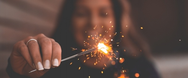 woman-holding-sparkler-in-front-of-camera600x250.jpg